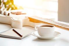 Gitarr, kaffe, notepad och blyertspenna Arkivbild