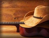Gitarr- och cowboyhatt på wood bakgrund Royaltyfria Bilder