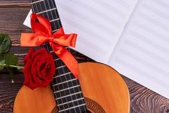 Gitarr och musikaliska anmärkningar på träbakgrund royaltyfria foton