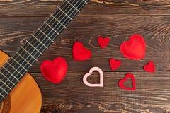 Gitarr och röda hjärtor på träbakgrund royaltyfria foton
