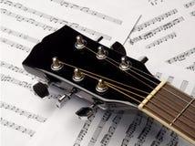 Gitarr på bakgrunden av ark med anmärkningar Arkivbilder
