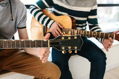 gitarr som lärer spelrum till Musikutbildning Arkivbild