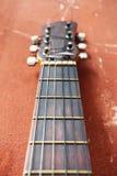Gitarre auf einem braunen Hintergrund Lizenzfreies Stockfoto