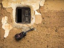 Gitarre, die an einem Fenster eines alten Hauses gemacht vom Holz und vom Lehm hängt Stockbilder