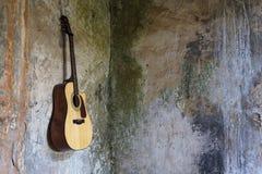 Gitarre hing an der Wand im defekten Haus Lizenzfreie Stockfotografie