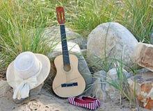 Gitarre mit Hut und Schuhen auf Strand Lizenzfreie Stockbilder