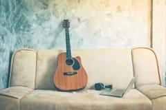 Gitarre mit Laptop und Kopfhörer auf einem Sofa Nicht tun sie schauen lecker Lizenzfreie Stockfotografie
