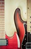 Gitarre mit zwei Rottönen auf einem hölzernen Hintergrund Stockfotografie