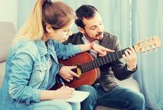 Gitarren handleder förklaring av grunderna till hans kvinnliga klient hemma Arkivfoto