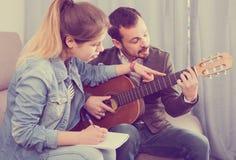 Gitarren handleder förklaring av grunderna till hans kvinnliga klient hemma Royaltyfria Foton