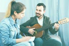Gitarren handleder förklaring av grunderna till hans kvinnliga klient hemma Royaltyfri Foto