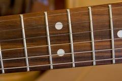 Gitarren-Schnüre auf einem Fretboard Stockbilder