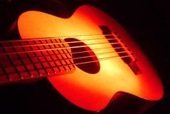Gitarren-Ukulele auf rotem Licht Stockbilder