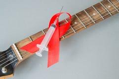 Gitarren vaggar musik, en injektionsspruta och det röda bandet - symbol av kampen mot HJÄLPMEDEL Fotografering för Bildbyråer