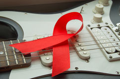 Gitarren vaggar musik och det röda bandet - symbol av kampen mot HJÄLPMEDEL Royaltyfri Foto