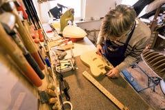 Gitarrenreparaturhauer, der das Sägemehl von einer E-Gitarre klärt Stockfotografie