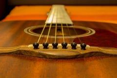 Gitarrenschnüre und nahes hohes des Sattels - braune Spitze/soundboard Stockfotos