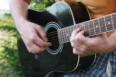 Gitarrenschnur-Mannhand im Freien Stockfotos