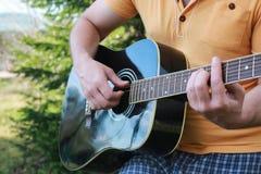 Gitarrenschnur-Mannhand im Freien Stockfoto