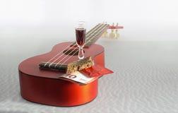 Gitarrenukulele, Brot, Eurobanknote, Glas mit einem Getränk und c Lizenzfreie Stockfotos