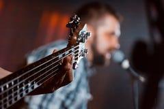 Gitarrfingerboard med rader och hand som spelar, suddig bakgrund på konserten i Vinnytsia, Ukraina, 24 01 2016 redaktörs- foto Royaltyfria Bilder