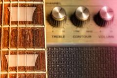 Gitarrfretboard och grinighetmarkördetalj, suddiga gamla förstärkareknoppar i bakgrunden royaltyfri bild
