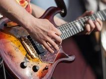 gitarrhand som rymmer mänsklig instrumentmusik royaltyfria bilder