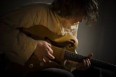 Gitarrist-barnet man att spela gitarren Arkivbild