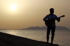 Gitarrist bei Sonnenaufgang auf dem Strand Lizenzfreies Stockfoto