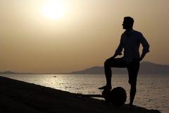 Gitarrist bei Sonnenaufgang auf dem Strand Stockfotografie