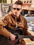 Gitarrist för musikgataaktörer som spelar gitarren fotografering för bildbyråer