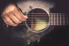 Gitarrist Hand som spelar på för fretboardtappning för akustisk gitarr stil royaltyfri fotografi