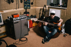 Gitarrist i gammal garagemusikstudio Arkivbild