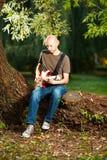 Gitarrist i parkera arkivbilder