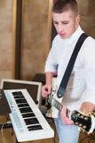 Gitarrist i studion som spelar gitarren bredvid tangentborden arkivfoto