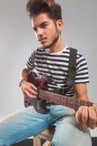 Gitarrist i studion som spelar hans instrument som bort ser arkivbilder