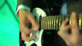 Gitarrist 4k spielt Akustikgitarre auf Nachtclubstadium, Blitze von Farblichtern