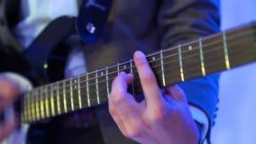 Gitarrist 4k spielt Akustikgitarre auf Nachtclubstadium, Blitze von Farblichtern stock footage