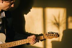 Gitarrist med den elektriska gitarren som hemma spelar royaltyfri fotografi