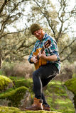 Gitarrist med den galna framsidan som spelar gitarren Royaltyfri Bild