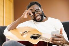Gitarrist med gitarren genom att använda mobilen royaltyfri fotografi