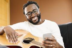 Gitarrist med gitarren genom att använda mobilen arkivfoto