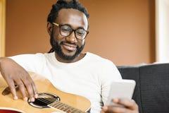 Gitarrist med gitarren genom att använda mobilen arkivfoton