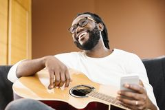 Gitarrist med gitarren genom att använda mobilen arkivbilder