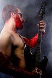 Gitarrist med svart för elektrisk gitarr, bärande framsida royaltyfria bilder
