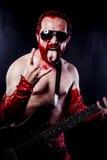 Gitarrist med svart för elektrisk gitarr, bärande framsidamålarfärg och rött royaltyfria bilder