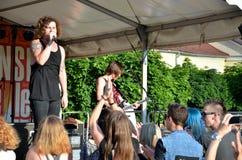 Gitarrist och tatuerad sångareställning framme av gruppen av tonåringar royaltyfri foto