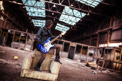 Gitarrist på övergiven byggnad royaltyfria bilder