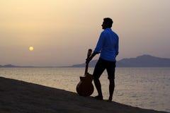 Gitarrist på soluppgång på stranden arkivfoto