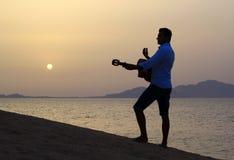 Gitarrist på soluppgång på stranden arkivbild